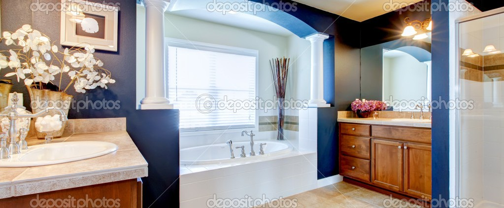Blue luxury bathroom with white tub, sink and shower.